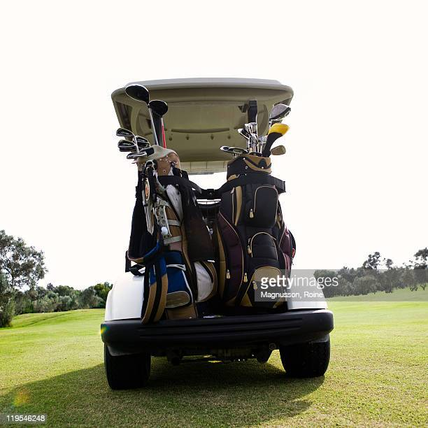 Golf bags on back of cart on golf course