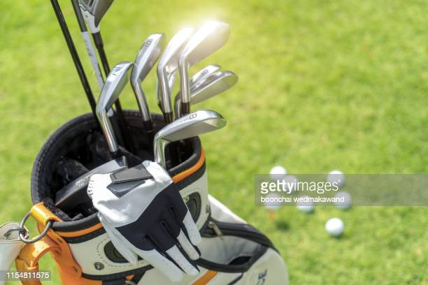 golf ball and golf club in bag on green grass - ゴルフクラブ ストックフォトと画像