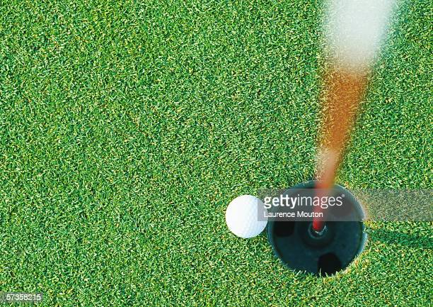 Golf ball at edge of hole, view from directly above