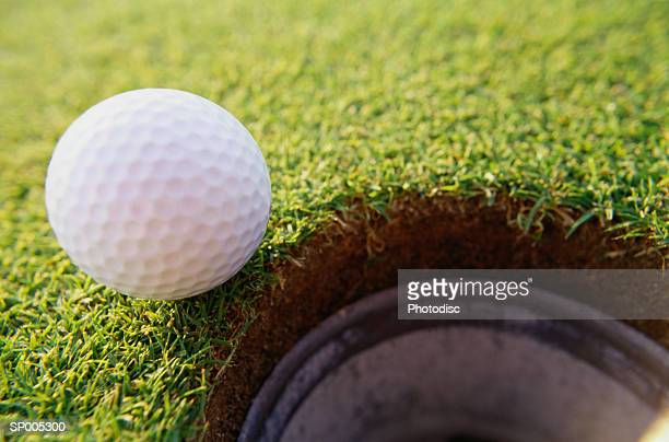 Golf Ball At the Edge of a Hole