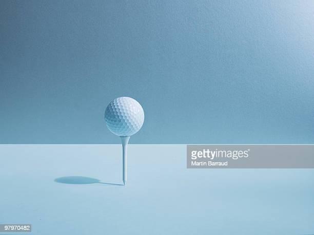 golf ball balancing on tee - golftee stock-fotos und bilder