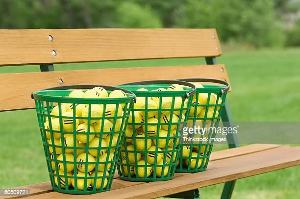 Golf ball baskets on bench