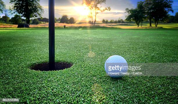 golf ball by hole on playing field - green golf course stock photos and pictures