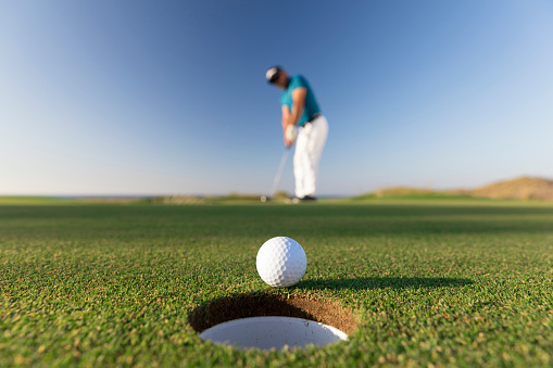 Golf ball entering the hole after successful stroke - Close up -  Links Golf 1070197874
