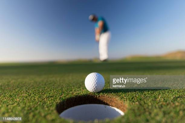 golf ball entering the hole after successful stroke - close up -  links golf - golf stock pictures, royalty-free photos & images