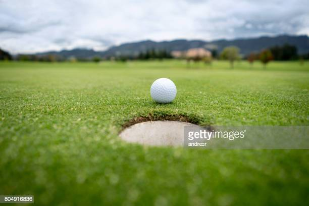 Golf ball going into the hole in the putting green