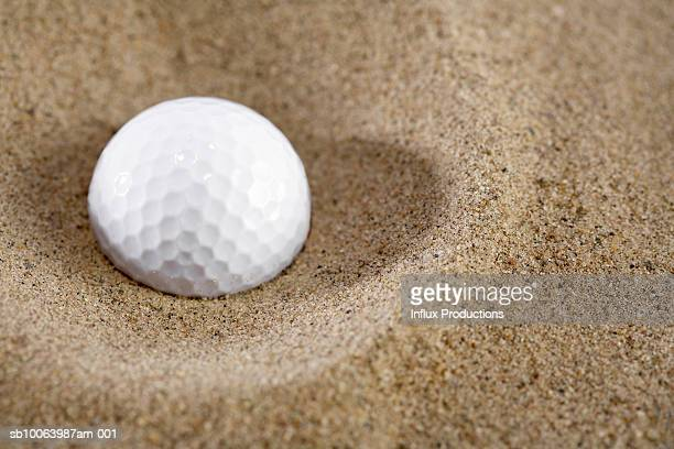 Golf ball in sand, close-up