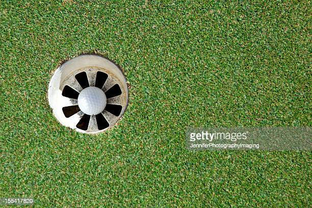 golf ball in the cup - putting green stock pictures, royalty-free photos & images