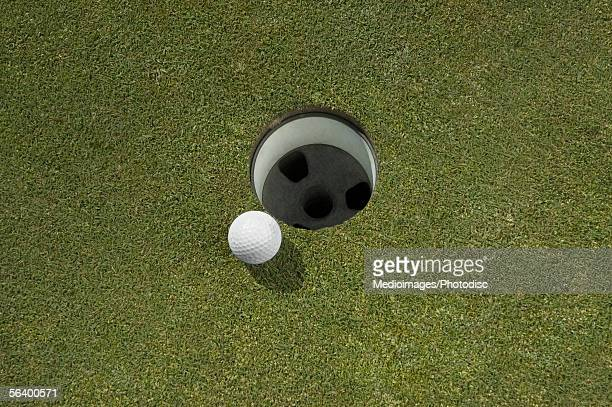 golf ball near hole, close-up - putting green stock pictures, royalty-free photos & images