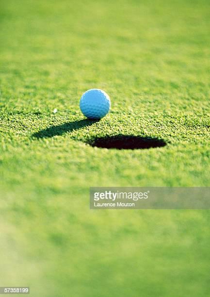 Golf ball near hole, close-up