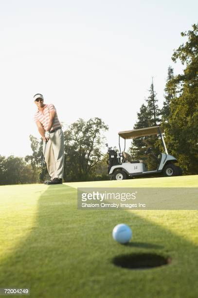 Golf ball next to hole with male golfer in background