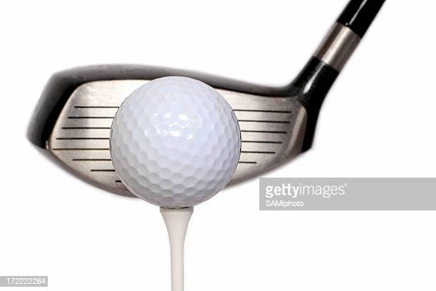 Golf ball on a tee with the head of a golf club next to it