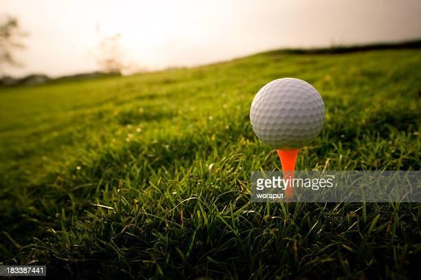 Golf ball on an orange tee in the grass