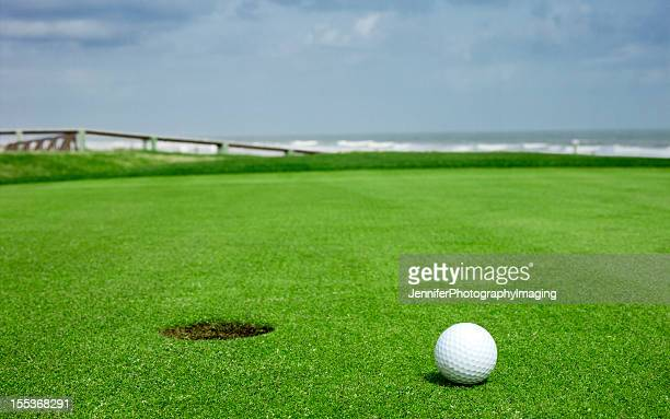 Golf ball on green close to the hole