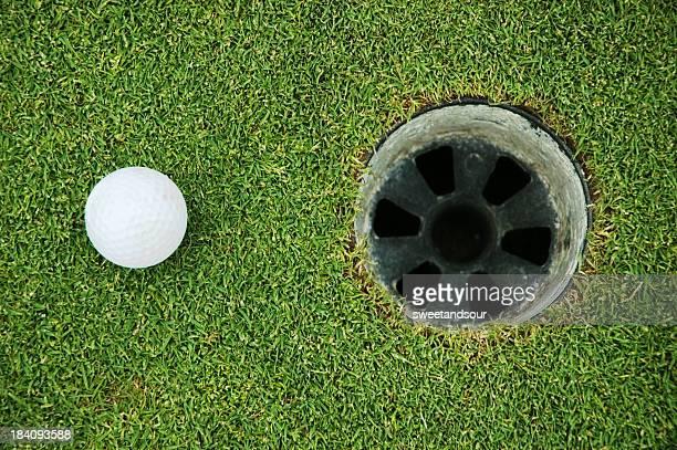 Golf ball on green grass near hole