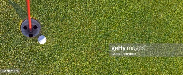 golf ball on green near cup panorama - golf background stock photos and pictures