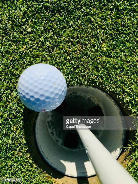 golf ball on green next to hole - putting green stock pictures, royalty-free photos & images