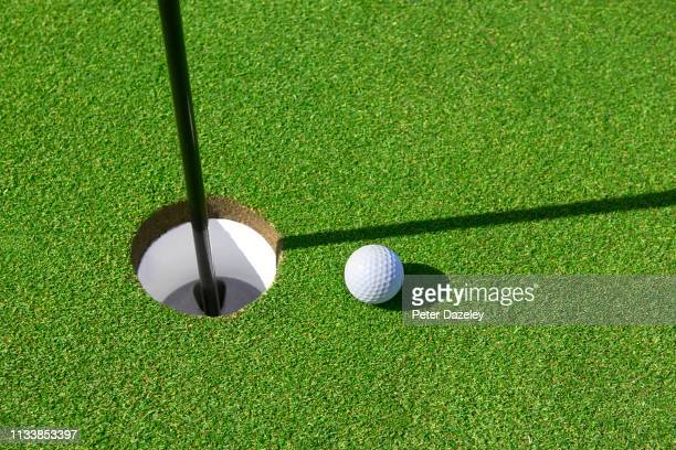 golf ball on green - putting stock pictures, royalty-free photos & images