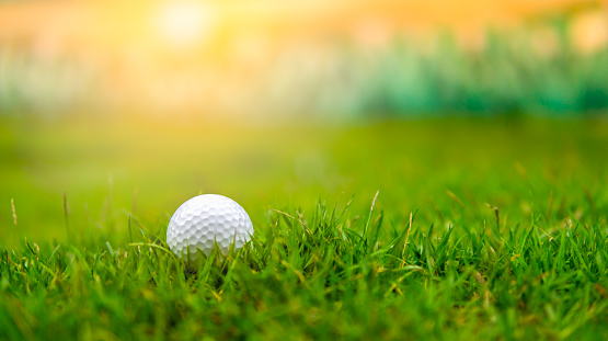 Golf ball on rough grass fairway on sunset 943418368