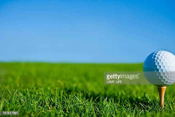golf ball on tee on grassy green - golf ball stock pictures, royalty-free photos & images