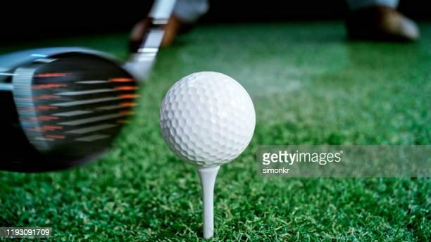 golfball auf abschlag - golftee stock-fotos und bilder