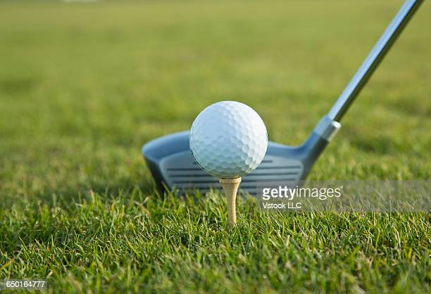 Golf ball on tee with golf club in background
