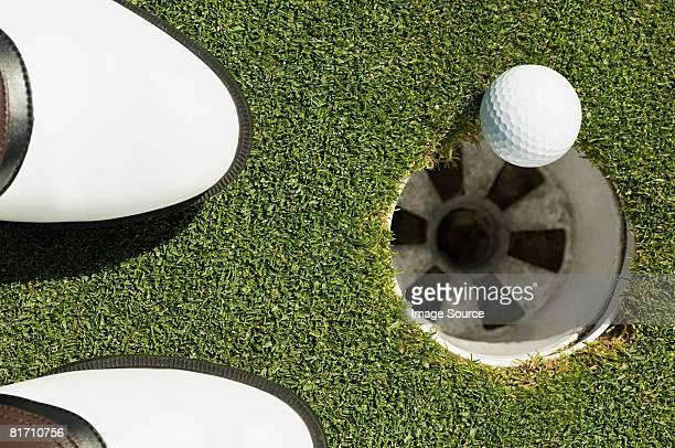 A golf ball on the edge of a hole
