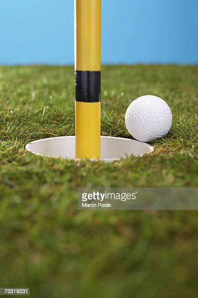 golf ball perched at edge of hole containing flag pole - martin stange stock-fotos und bilder