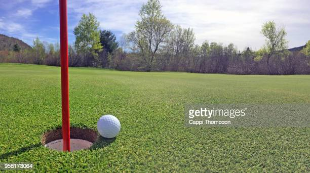 Golf ball resting between flag stick pin and cup panorama