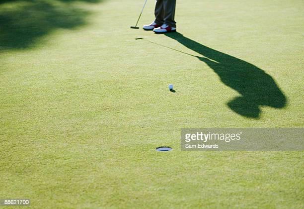 Golf ball rolling toward cup
