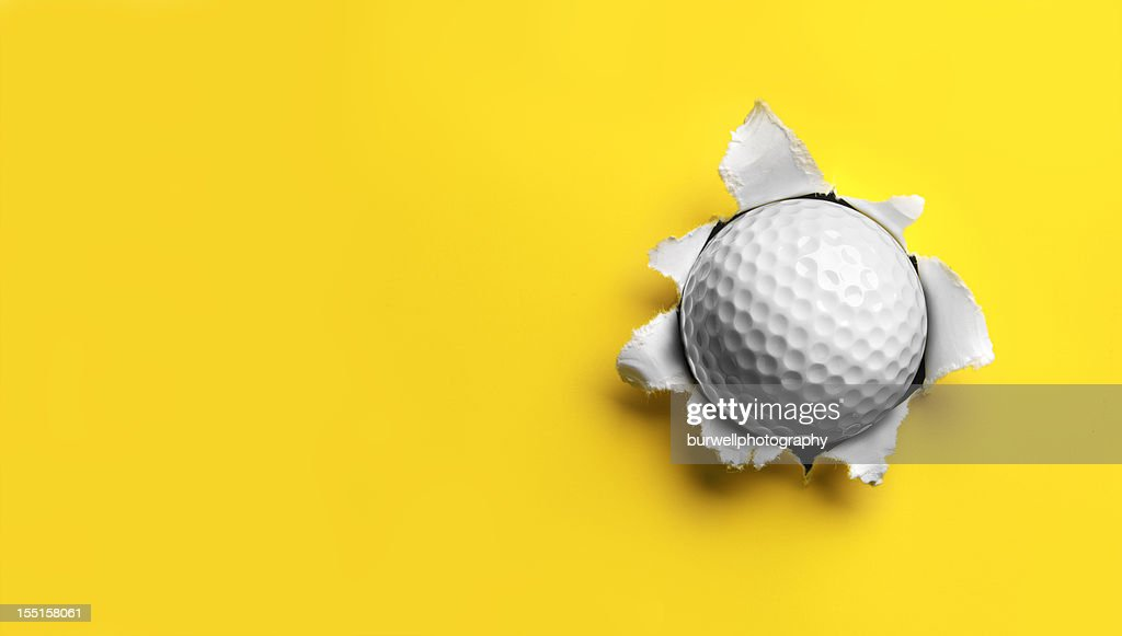 Golf Ball Feststecken in Gelbes Papier : Stock-Foto