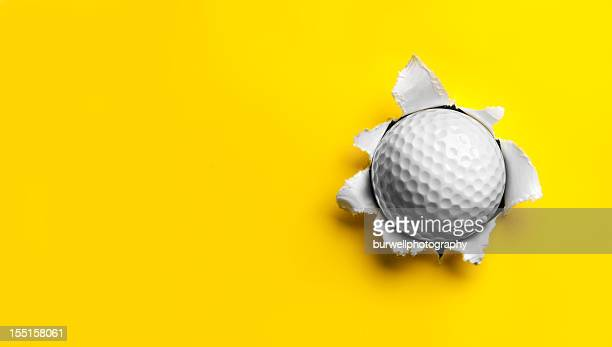 golf ball stuck in yellow paper - sports ball stock pictures, royalty-free photos & images