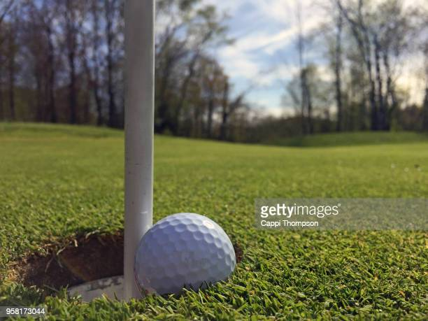 Golf ball wedged between pin and cop