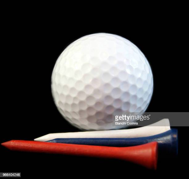 A golf ball with red and blue tee on black background