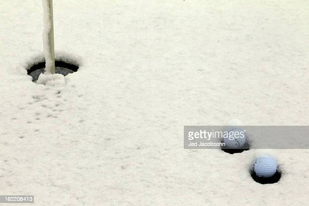 Golf balls are seen in the snow on the practice putting green as play was suspended due to weather during the first round of the World Golf...