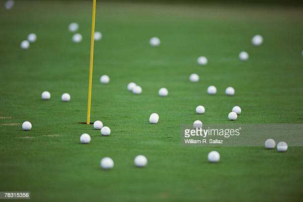 golf balls on putting green - driving range stock photos and pictures