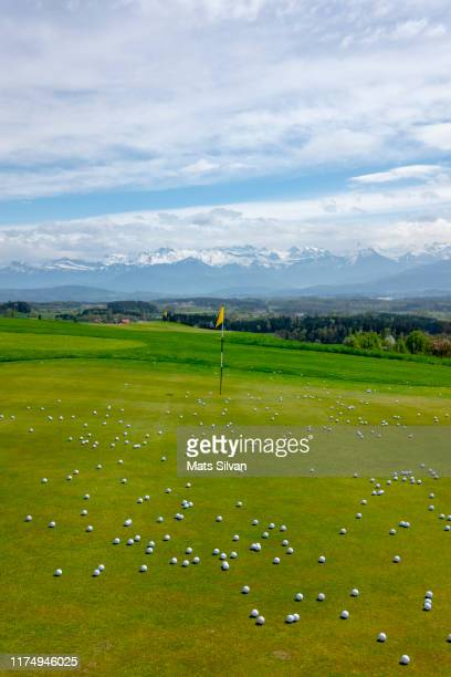 golf balls on putting green with golf flag and snow-capped mountain - driving range stock pictures, royalty-free photos & images