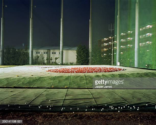 golf balls strewn across driving range, night - ゴルフ練習場 ストックフォトと画像