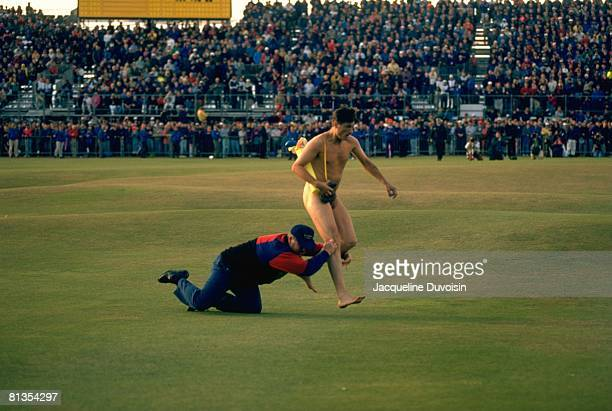 Golf British Open Male streaker Mark Roberts getting tackled by police officer on green during Sunday play St Andrews GBR 7/23/1995