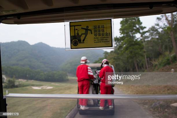 Golf caddies ride on a golf cart at Mission Hills Dongguan operated by Mission Hills Group Ltd in Dongguan Guangdong province China on Friday Dec 21...