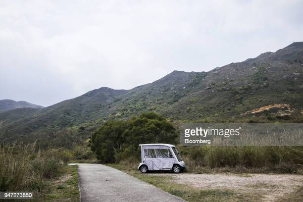 A golf cart stands parked next to a hiking trail in Discovery Bay a residential project developed by Hong Kong Resort Co on Lantau Island in Hong...