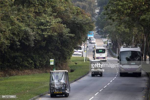 Golf carts and buses travel along a road in Discovery Bay a residential project developed by Hong Kong Resort Co on Lantau Island in Hong Kong China...