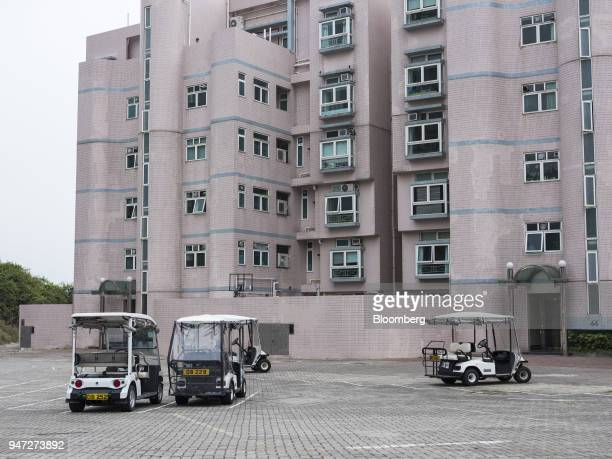 Golf carts stand parked in front of an apartment building in Discovery Bay a residential project developed by Hong Kong Resort Co on Lantau Island in...
