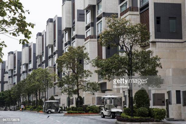 Golf carts stand parked in front of lowrise buildings in Discovery Bay a residential project developed by Hong Kong Resort Co on Lantau Island in...
