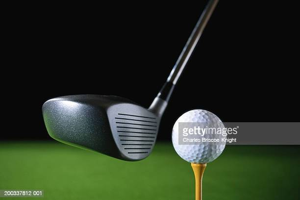 golf club driver held by ball on tee, close-up - driver golf club stock pictures, royalty-free photos & images