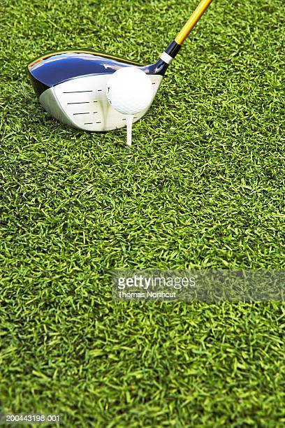 Golf club, golf ball and tee on artificial turf