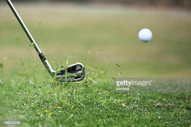 Golf Club Hits Ball in the Air with Grass Flying