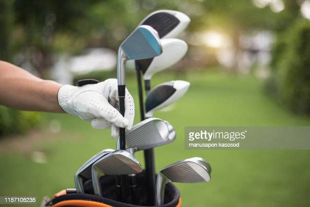 golf clubs drivers over green field background - driver golf club stock pictures, royalty-free photos & images