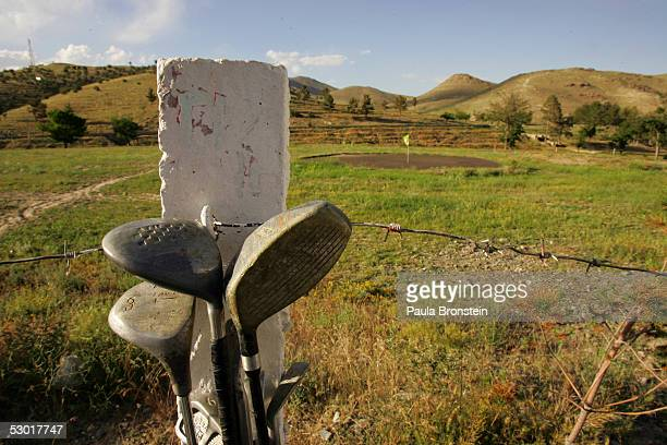 Golf clubs lean against a barbed wire fence waiting to be used at the Kabul Golf Club June 3 2005 in Kabul Afghanistan The Kabul Golf Club has been...