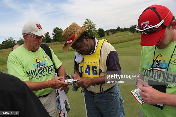 Golf coach Glenn Paulus assists visually impared military veteran Wilber Eugene with signing his score card following the golf competition at the...